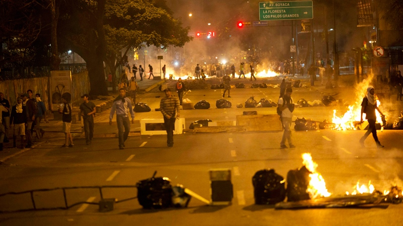 Objects placed by opposition protesters block a road in the Altamira neighborhood of Caracas, Venezuela, Thursday, Feb. 20, 2014. (AP Photo/Rodrigo Abd)