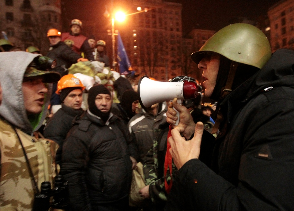 Opposition lawmaker Andriy Parubiy, right, tries to convince protesters to let a group of policemen, captured earlier Thursday, go in Kyiv, Ukraine, Friday, Feb. 21, 2014.  (AP / Sergei Chuzavkov)