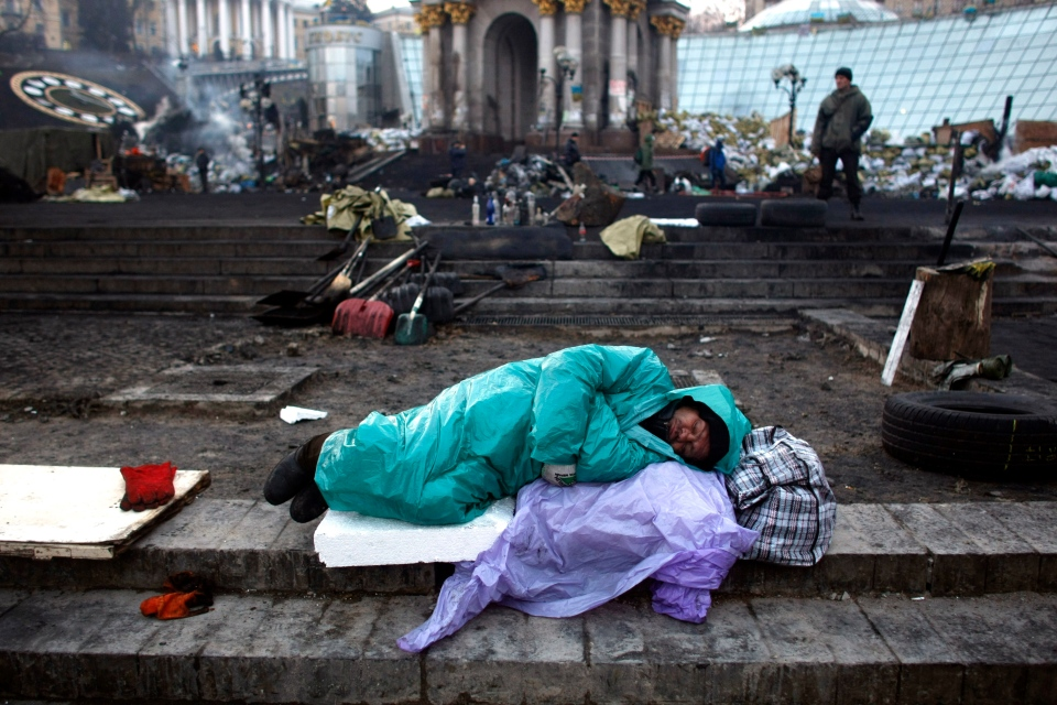 An anti-government protester sleeps at the Independence Square in Kiev, Ukraine, Friday, Feb. 21, 2014. (AP / Marko Drobnjakovic)