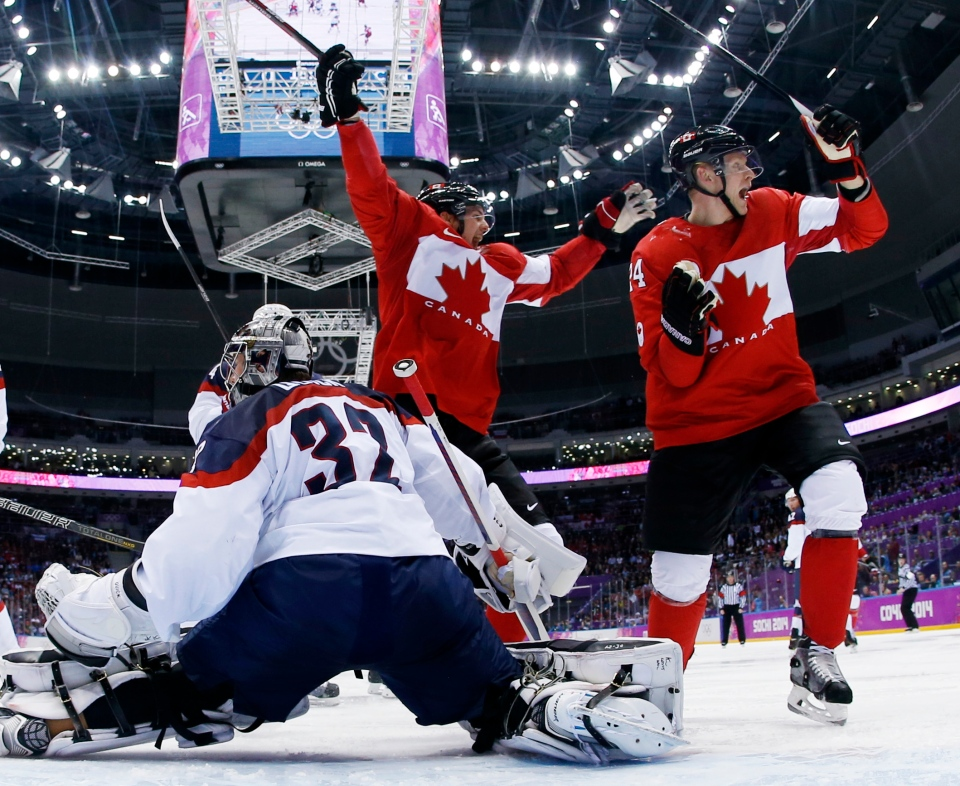 Team Canada forward Benn Jamie, left, reacts after scoring a goal in front of U.S. goaltender Jonathan Quick of a men's semifinal ice hockey game at the 2014 Winter Olympics, Friday, Feb. 21, 2014, in Sochi, Russia. (AP / Julio Cortez)