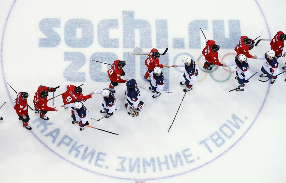 USA and Canada players shake hands after a men's semifinal ice hockey game at the 2014 Winter Olympics, Friday, Feb. 21, 2014. (AP / David J. Phillip )