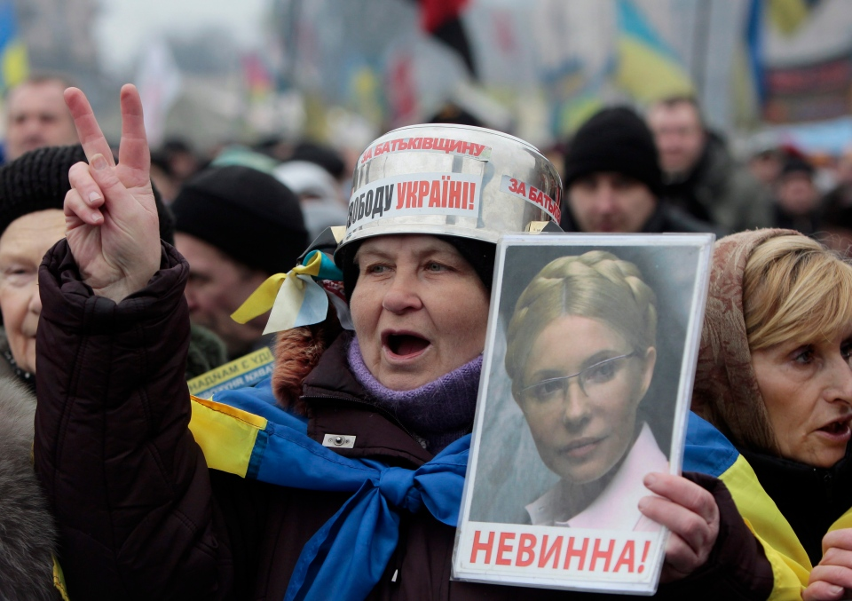 Opposition supporters, one holding a portrait of former prime minister Yulia Tymoshenko, shout slogans during a rally in the Independence Square in Kyiv, Ukraine, Sunday, Feb. 9, 2014. (AP / Sergei Chuzavkov)