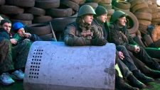 Protesters rest at a barricade in Kyiv, Ukraine