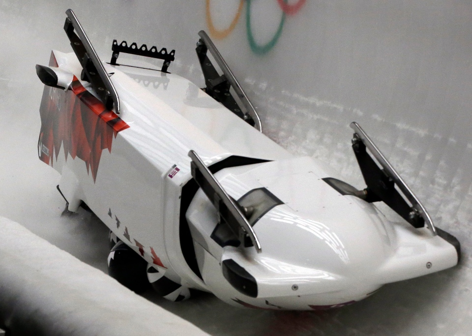 The team from Canada CAN-3, with Justin Kripps, Jesse Lumsden, Cody Sorensen and Ben Coakwell, slide down the track upside down after crashing in turn sixteen during the men's four-man bobsled competition at the 2014 Winter Olympics in Krasnaya Polyana, Russia on Saturday, Feb. 22, 2014. (AP / Dita Alangkara)