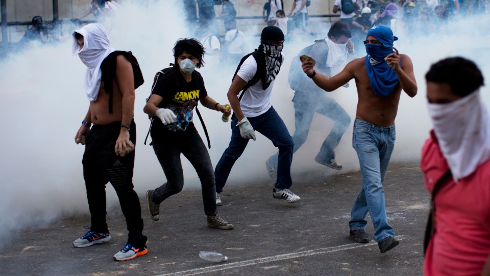 A group of masked men run for cover after riot police launched tear gas in Caracas, Venezuela, Saturday, Feb. 22, 2014. (AP / Rodrigo Abd)
