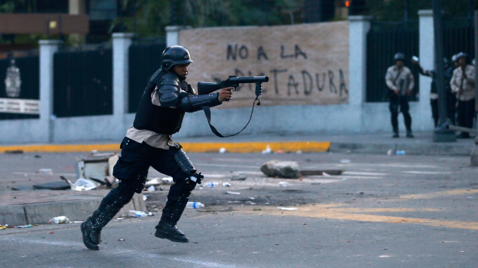 A policeman fire a tear gas canister to demonstrators during an anti-government protest in Caracas, Venezuela, Saturday, Feb. 22, 2014. (AP / Fernando Llano)