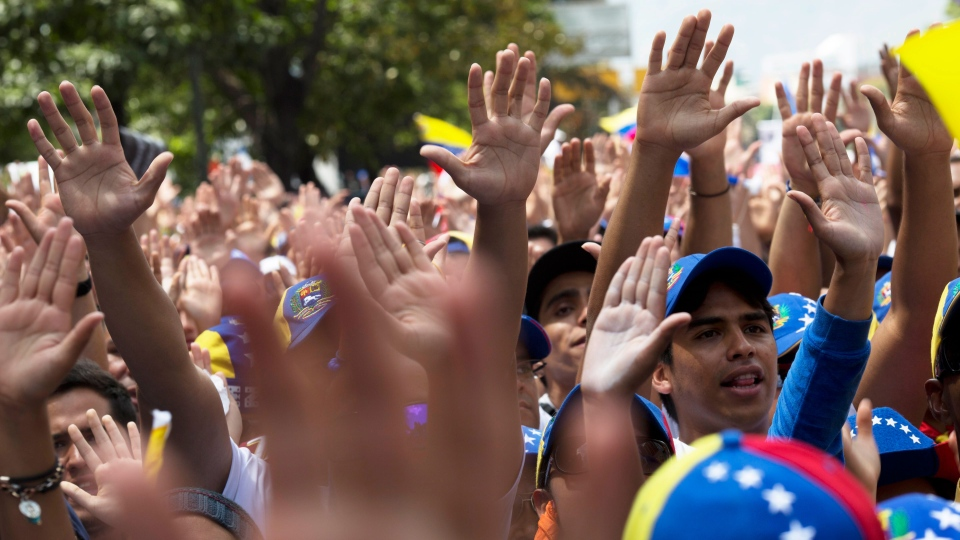 Opposition demonstrators raise their hands during a rally in Caracas, Venezuela, Saturday, Feb. 22, 2014. (AP / Rodrigo Abd)