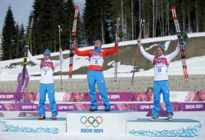 Russia's gold medal winner Alexander Legkov is flanked by Russia's silver medal winner Maxim Vylegzhanin, left and Russia's bronze medal winner Ilia Chernousov during the flower ceremony of the men's 50K cross-country race at the 2014 Winter Olympics on Feb. 23, 2014, in Krasnaya Polyana, Russia. (AP Photo/Gregorio Borgia)