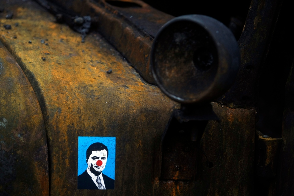 A sticker depicting Ukrainian President Viktor Yanukovych is placed on a burned military truck in Kyiv, Ukraine on Feb. 23, 2014. (AP / Marko Drobnjakovic)