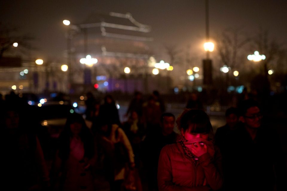 A woman, illuminated by neon lights, presses her scarf to cover her mouth and nose on a hazy day in central Beijing, China on Feb. 22, 2014. (AP / Alexander F. Yuan)