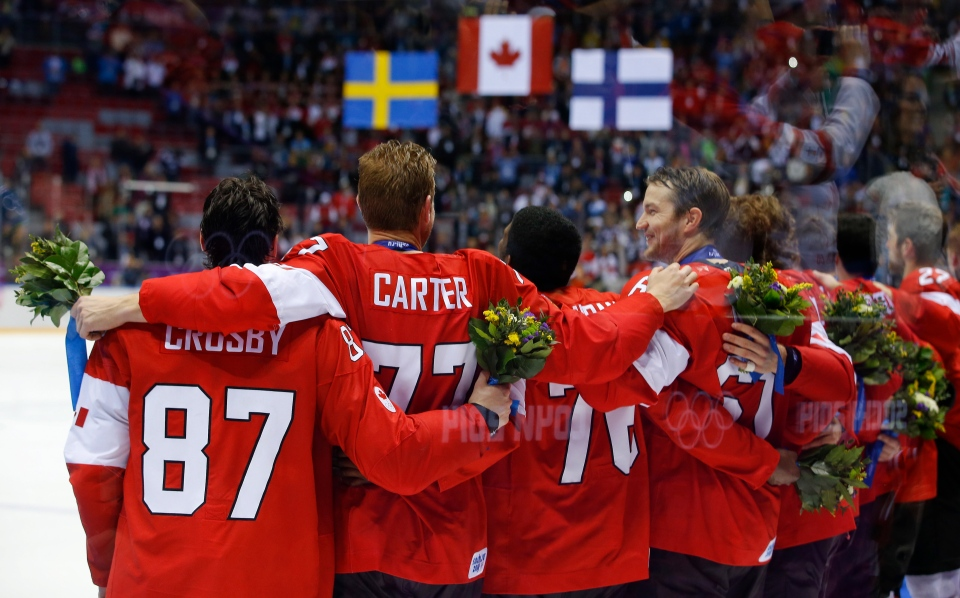 Team Canada locks arms during the playing of the Canadian national anthem after Canada beat Sweden 3-0 in the men's gold medal ice hockey game at the 2014 Winter Olympics, Sunday, Feb. 23, 2014, in Sochi, Russia. (AP / Matt Slocum)