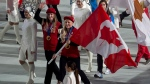 Bobsledders Kaillie Humphries (right) and Heather Moyse carry the Canadian flag into the stadium for the closing ceremonies for the Sochi Winter Olympics on Feb. 23, 2014. (Adrian Wyld / THE CANADIAN PRESS)