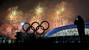 Man takes a photograph of fireworks during the closing ceremony of the 2014 Winter Olympics, Sunday, Feb. 23, 2014, in Sochi, Russia. (AP / Petr David Josek)