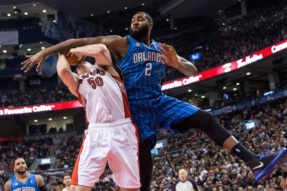Toronto Raptors' Tyler Hansbrough (left) is fouled by Orlando Magic's Kyle O'Quinn during first half NBA basketball action in Toronto on Sunday, Feb. 23, 2014. (Chris Young / THE CANADIAN PRESS)