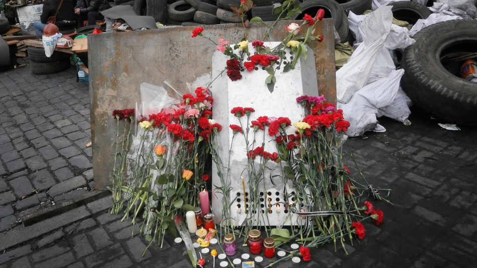 Flowers cover a protester's shield on the site where he was killed by a riot police sniper during a recent deadly clash close to Kyiv's Independence Square, Ukraine, on a mourning day Sunday, Feb. 23, 2014. (AP / Efrem Lukatsky)