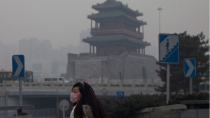 A woman wears a mask as she walks under smog in Beijing, China, Saturday, Feb. 15, 2014. (AP / Alexander F. Yuan)