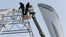 Workers near the Olympic flame cauldron in Sochi