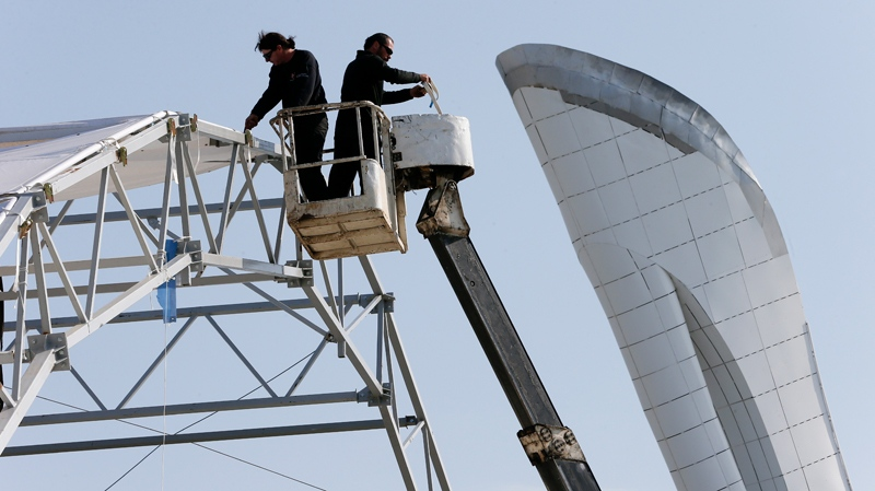 Workers take down a structure near the Olympic flame cauldron the day after the closing ceremony for the 2014 Winter Olympics, Monday, Feb. 24, 2014, in Sochi, Russia. (AP Photo/Mark Humphrey)