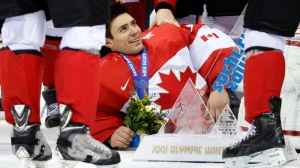 Canada goalie Carey Price lies on the ice with his team's trophy after beating Sweden 3-0 in the men's ice hockey gold medal game at the 2014 Winter Olympics, Sunday, Feb. 23, 2014, in Sochi, Russia. (AP Photo/Mark Humphrey)