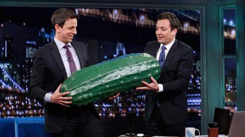 "This image released by NBC shows Seth Meyers, left, receiving a giant plastic pickle prop by host Jimmy Fallon during an appearance on ""Late Night with Jimmy Fallon,"" Tuesday, Jan. 28, 2014, in New York. (AP Photo/NBC, Lloyd Bishop)"