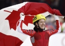 Anouk Leblanc-Boucher, who now goes by Anouk English, skates around the ice with the Canadian flag as she celebrates her bronze medal win in the ladies 500-metre relay final in short track speed skating at the 2006 Winter Olympic Games. (CP / Paul Chiasson)