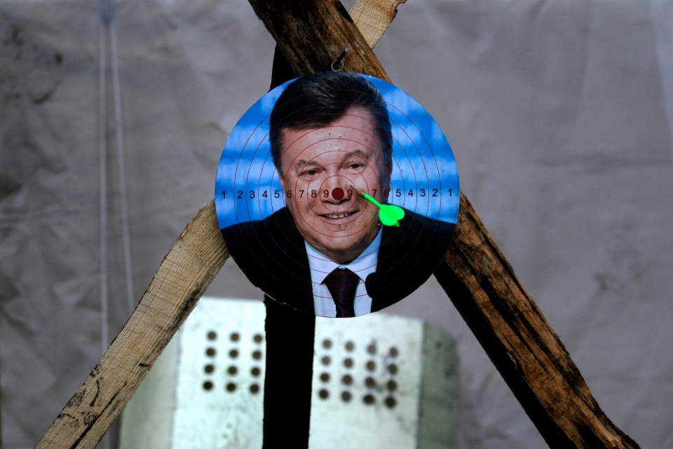 A portrait of Ukraine's embattled president Viktor Yanukovych is used for a game of darts at Independence Square in Kiev, Ukraine, Monday, Feb. 24, 2014. (AP / Marko Drobnjakovic)