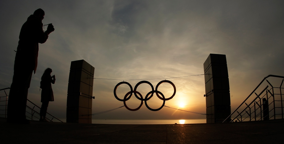 People take photos of a set of Olympic Rings at a train station overlooking the Black Sea a day after the close of the 2014 Winter Olympics, in Sochi, Russia, Monday, Feb. 24, 2014. (AP / Charlie Riedel)
