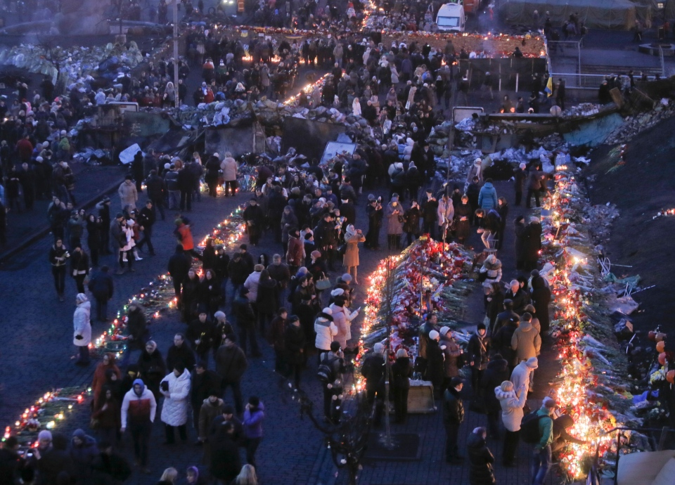 People lay flowers and lit candles at one of the barricades leading to Independence Square, Kiev,the epicenter of the country's recent unrest, on a mourning day Monday, Feb. 24, 2014.  (AP / Efrem Lukatsky)
