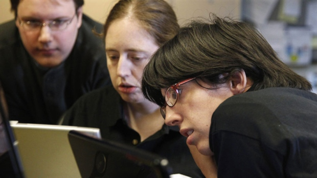 In this photo taken Thursday, Sept. 8, 2011, Aspiritech employees, from left, Rick Alexander, Katie Levin, and Jamie Specht work together at the nonprofit enterprise that specializes in finding software bugs as they test a new program in Highland Park, Ill. (AP Photo/M. Spencer Green)