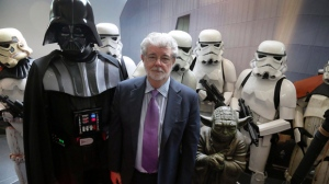 """""""Star Wars""""creator George Lucas poses with characters from the movies """"Star Wars"""" during the opening ceremony of the """"Sandcrawler"""" building, Thursday, Jan. 16, 2014 in Singapore. (AP Photo/Wong Maye-E)"""