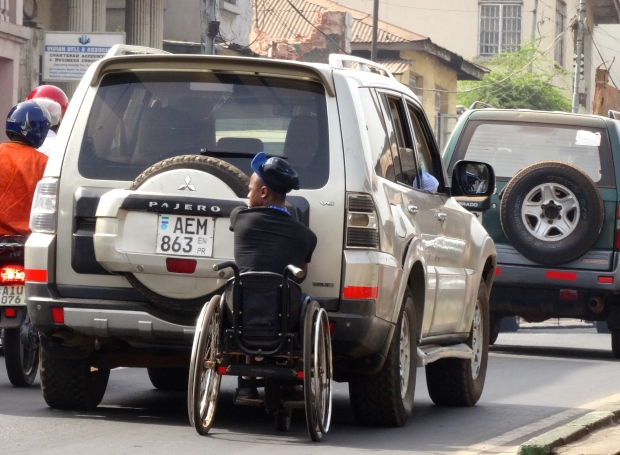 A man in a wheelchair grabs onto a bumper