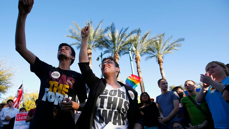 Anthony Musa, left, and Brianna Pantillione join nearly 250 gay rights supporters protesting SB1062 at the Arizona Capitol in Phoenix, Friday, Feb. 21, 2014. (AP / Ross D. Franklin)