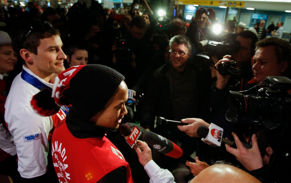 Long track speedskaters Denny Morrison, left, and Gilmore Junio talk with media after arriving home to Calgary from the Sochi Games on Feb. 25, 2014. (Jeff McIntosh / THE CANADIAN PRESS)