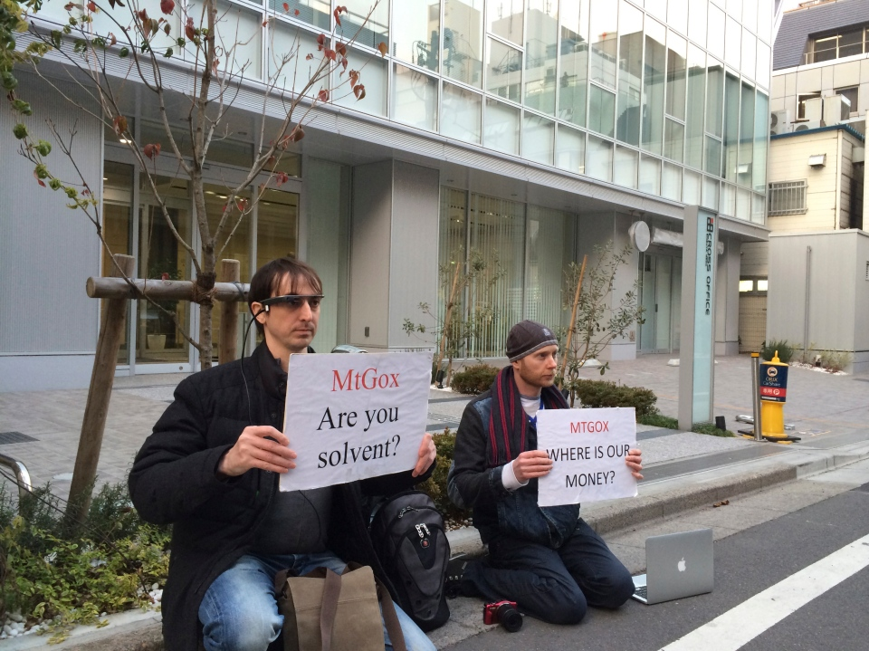 Bitcoin trader Kolin Burges, right, of London and American Aaron (only his first name was given) hold protest signs as they conduct a sit-in in front of the office tower housing Mt. Gox in Tokyo Tuesday, Feb. 25, 2014. (AP / Kaori Hitomi)