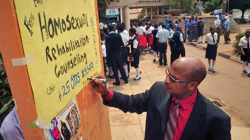 Ugandan anti-gay activist Pastor Martin Ssempa posts up a public notice offering 'rehabilitation' for homosexuals at Uganda's National Theatre in Kampala, Uganda Tuesday, Feb. 25, 2014. (AP Photo/Stephen Wandera)