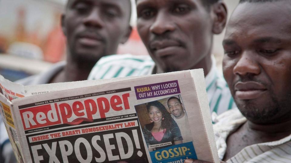 "A Ugandan reads a copy of the ""Red Pepper"" tabloid newspaper in Kampala, Uganda Tuesday, Feb. 25, 2014. (AP / Rebecca Vassie)"