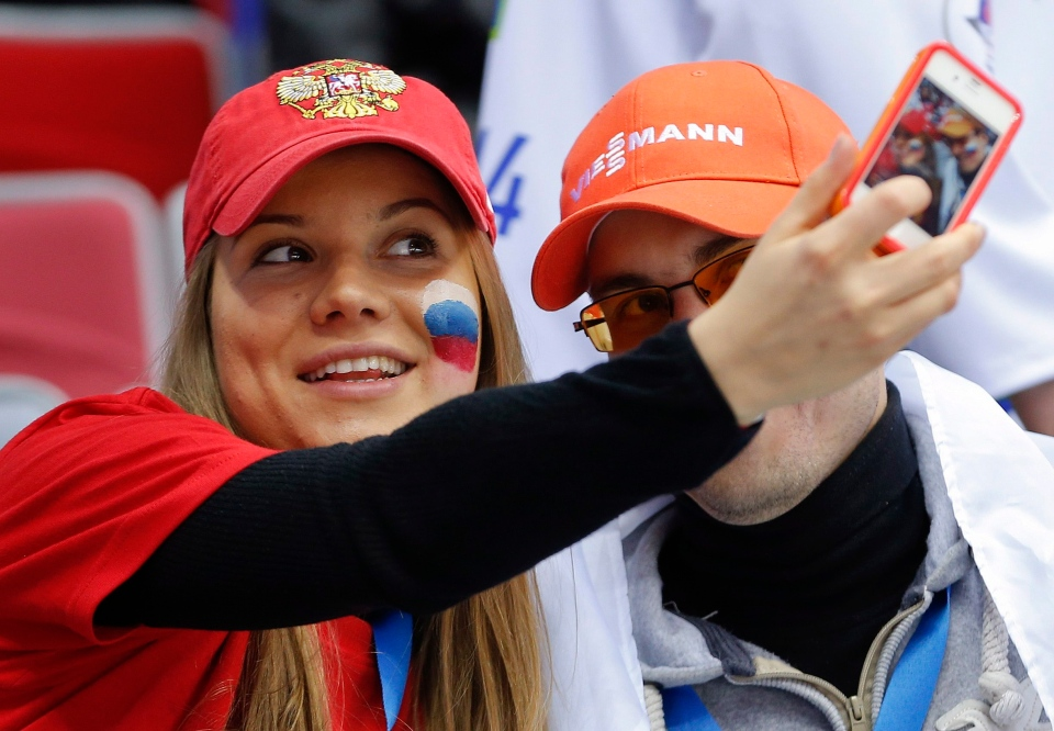 These selfie-taking hockey fans don't have lice, but some experts say constantly taking pictures with your friends can pass the bugs around. (AP/Julio Cortez)