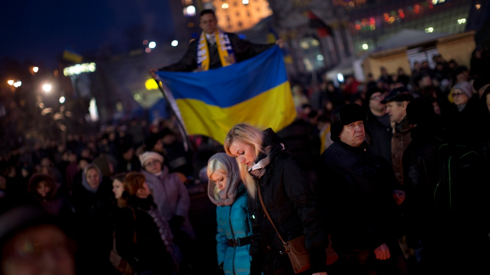 People walk at a memorial for the people killed in clashes with the police at the Independence Square, the epicenter of the country's current unrest, in Kyiv, Ukraine, Wednesday, Feb. 26, 2014. (AP / Emilio Morenatti)