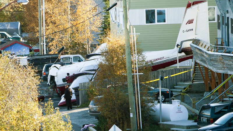RCMP officers inspect the wreckage of an Arctic Sunwest plane crash that claimed the lives of two people and injured seven others in Yellowknife on Thursday Sept., 22, 2011. (James Mackenzie / THE CANADIAN PRESS)