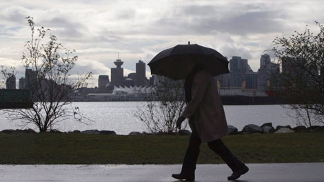 File. Under cloudy skies and heavy rain a pedestrian makes her way along the shoreline in North Vancouver, B.C. THE CANADIAN PRESS/Jonathan Hayward