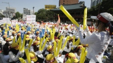 South Korean prostitutes wearing caps and masks to cover their identities raise their balloon sticks in a rally against the enacted anti-prostitution law in Seoul, South Korea, Thursday, Sept. 22, 2011. (AP Photo/Ahn Young-joon)