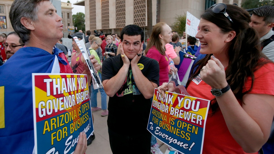 Demonstrators celebrate in different ways as they learn Arizona Republican Gov. Jan Brewer vetoes SB1062, a bill designed to give added protection from lawsuits to people who assert their religious beliefs in refusing service to gays, at the Arizona Capitol on Wednesday, Feb. 26, 2014, in Phoenix. (AP Photo/Ross D. Franklin)