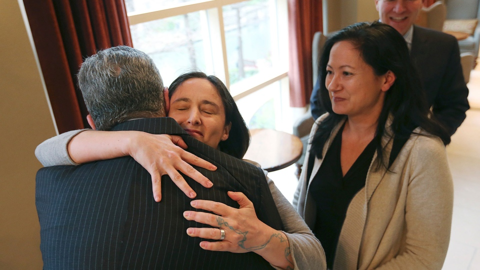 Nicole Dimetman hugs attorney Barry Chasnoff as her partner, Cleopatra De Leon, waits to greet him before a press conference in San Antonio on Wednesday, Feb. 26, 2014, after U.S. Federal Judge Orlando Garcia declared a same-sex marriage ban in deeply conservative Texas unconstitutional. (San Antonio Express-News / Jerry Lara)