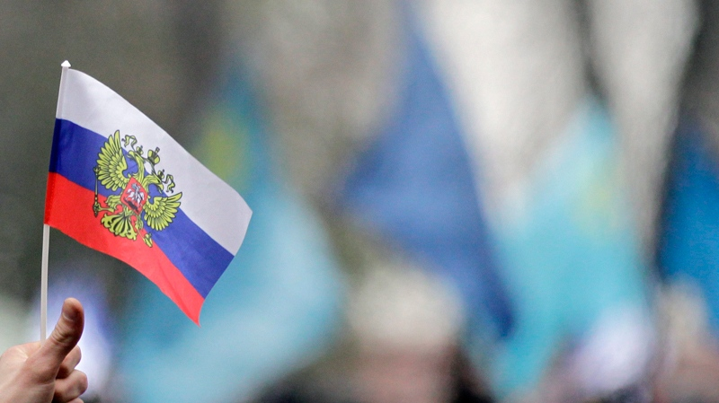 A Pro-Russian demonstrator holds up a Russian flag during a protest in front of a local government building in Simferopol, Crimea, Ukraine, Wednesday, Feb. 26, 2014.  (AP Photo/Darko Vojinovic)
