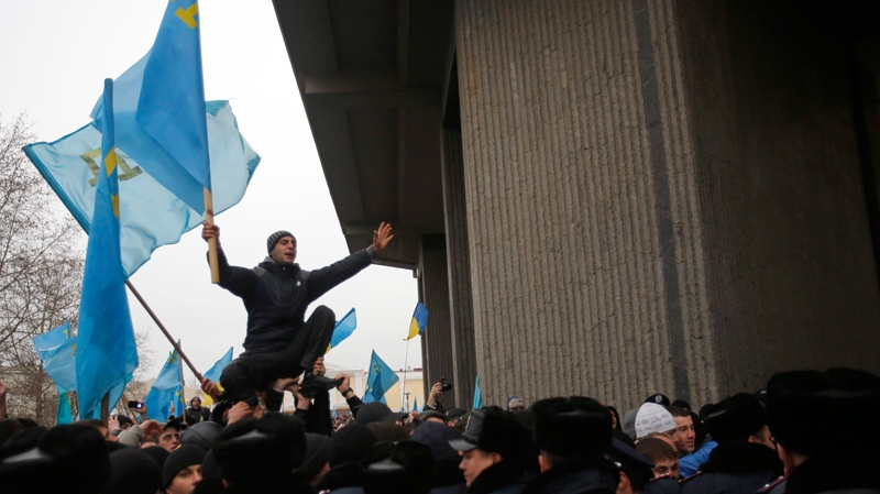 A Crimean Tatar shouts slogans and waves the ethnic flag of the Crimean Tatars during a protest in front of a local government building in Simferopol, Crimea, Ukraine, Wednesday, Feb. 26, 2014. (AP Photo/Darko Vojinovic)