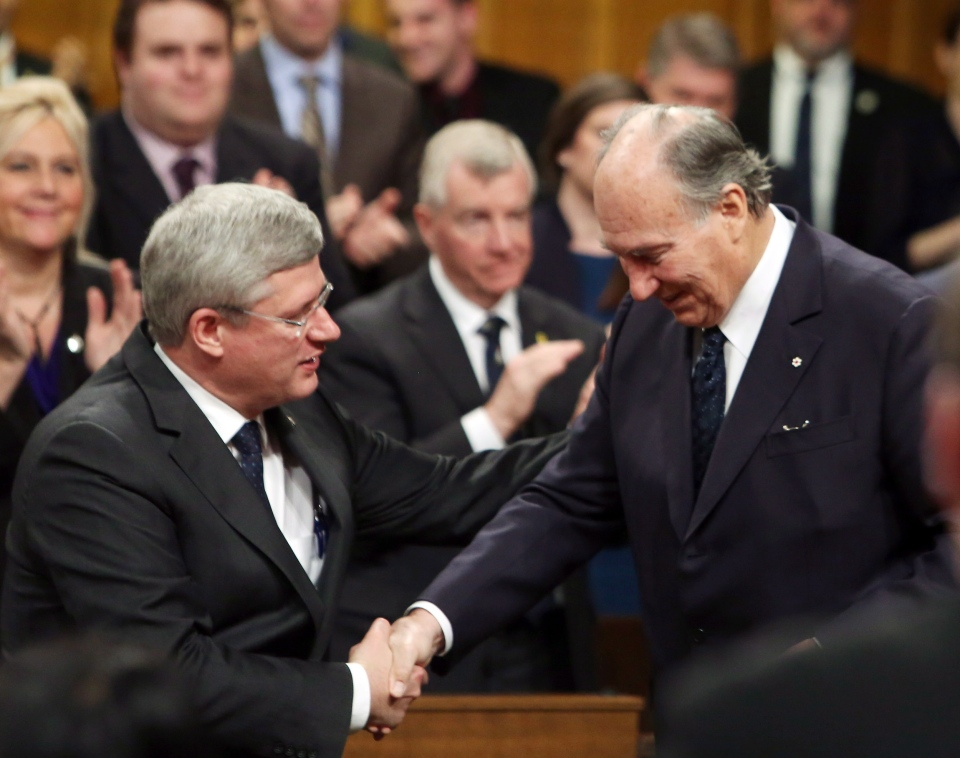 Prime Minister Stephen Harper (left) give a helping hand to the Aga Khan (right), spiritual leader of the world's 15-million Shia Ismaili Muslims, after the Aga Khan addressed the House of Commons, on Parliament Hill in Ottawa, Thursday, Feb. 27, 2014. (Fred Chartrand / THE CANADIAN PRESS)