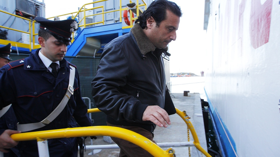 Captain Francesco Schettino, right, is followed by Italian Carabinieri as he boards a ferry on the Island of Giglio, off the Italian coast in Tuscany, Thursday, Feb. 27, 2014. (AP / Andrew Medichini)