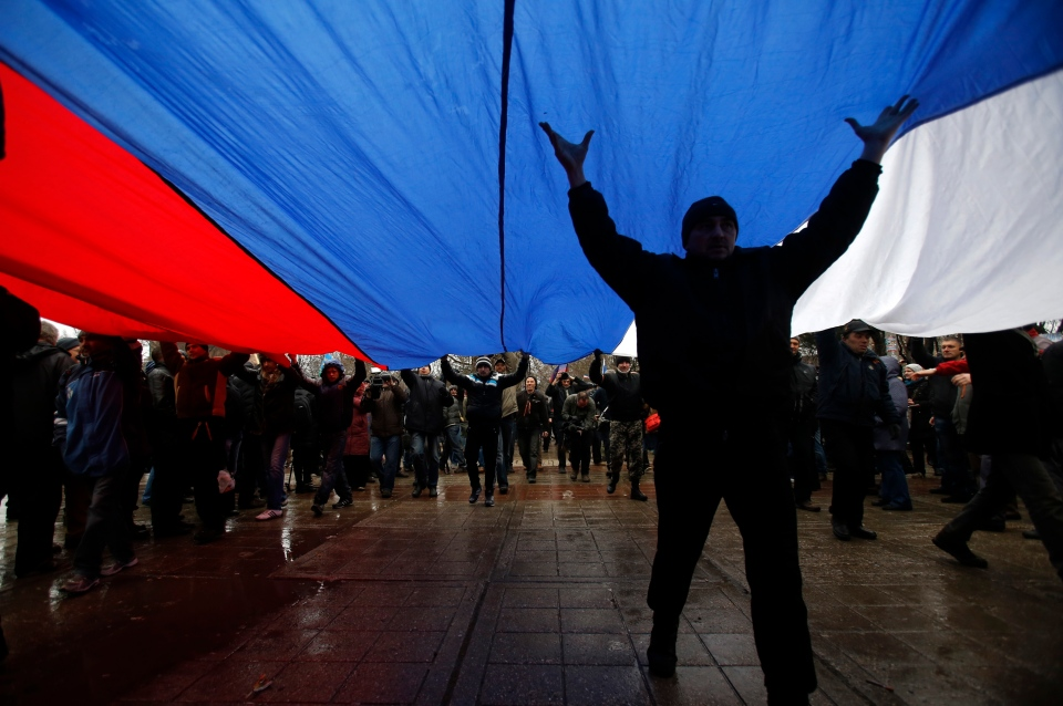 Pro-Russian demonstrators march with a huge Russian flag during a protest in front of a local government building in Simferopol, Crimea, Ukraine, Thursday, Feb. 27, 2014. (AP /Darko Vojinovic)