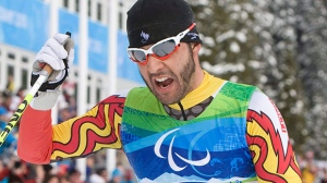 Canadian Brian McKeever celebrates his gold medal win in the men's 20 km free, visually impaired cross country ski race at the 2010 Winter Paralympic Games in Whistler, Monday, March 15, 2010. (Jonathan Hayward / THE CANADIAN PRESS)