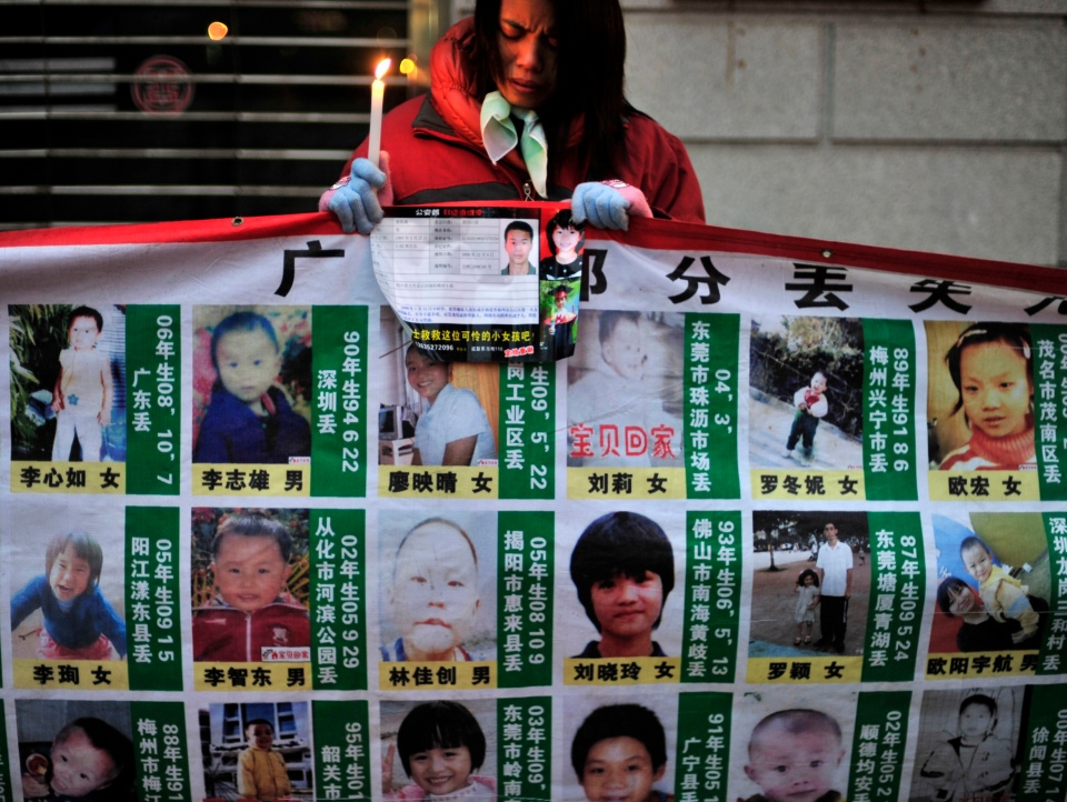 In this Jan. 24, 2010 file photo, a woman holds a candle behind a board showing photos of missing children during a campaign to spread the information to search for them in Wuhan, in central China's Hubei province. (AP Photo, File)